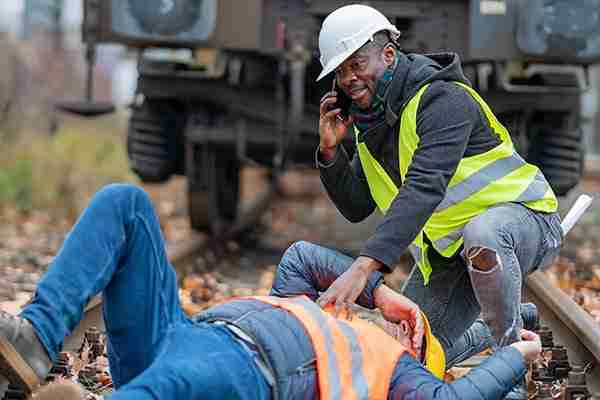 Personal-injury-attorney-faq-construction-working-calling-for-help-on-railroad-tracks-while-coworkers-lies-on-ground