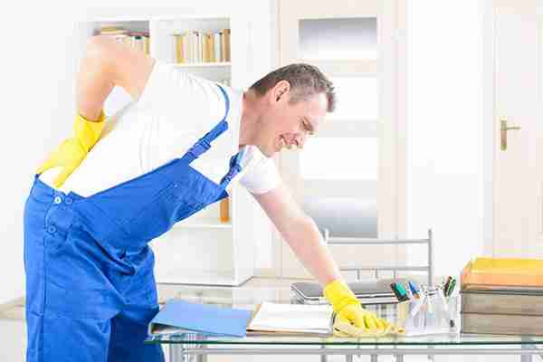 workplace-injury-lawyer-man-leaning-over-from-back-injury-while-cleaning